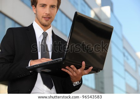Young business outside office with laptop computer