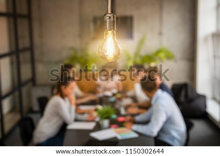 Young business people are discussing together a new startup project. A glowing light bulb as a new idea.