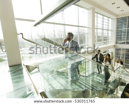 Young business people climb the stairs in the office building