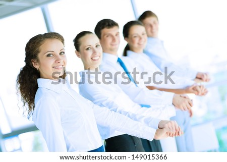 young business people holding hands, standing in a row, the concept of teamwork
