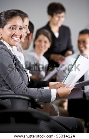 Young business people or college students sitting in row reading report in presentation