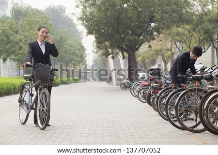 Young Business people parking their bikes and talking on the phone in Beijing