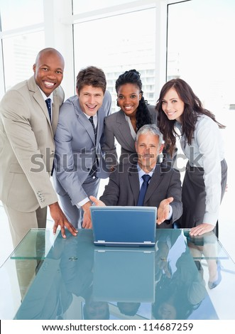 Young business people standing behind their director proudly showing the laptop