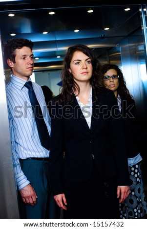 Young business people standing in elevator.