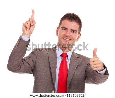 young business pointing something above his head and showing thumbs up gesture, while smiling at the camera
