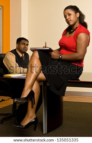 Young business professional giving his secretary direction as she takes notes.