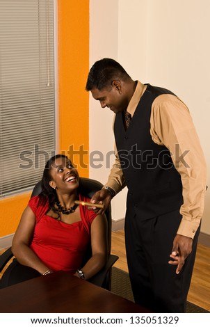 Young business professional offering his secretary a cigar.