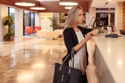 Young business stylish girl dissatisfied with service in Bank. Poor customer support. A woman is late for a corporate meeting, demands a complaint book for an bad review of hotel and its employees
