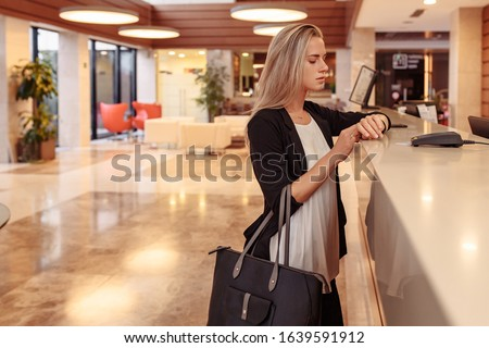 Young business stylish girl dissatisfied with service in Bank. Poor customer support. A woman is late for a corporate meeting, demands a complaint book for an bad review of hotel and its employees Foto stock ©