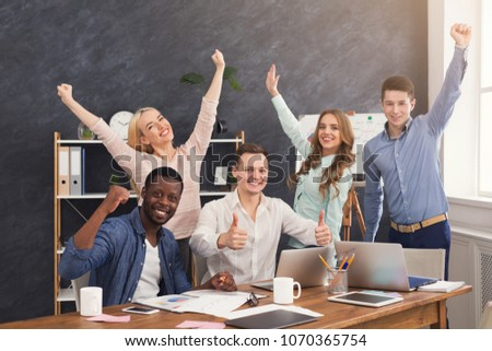 Young business team enjoying success, looking at computer screen, celebrating successful project, dealing contract, winning tender, copy space #1070365754