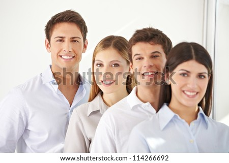 Young business team standing behind each other in a row