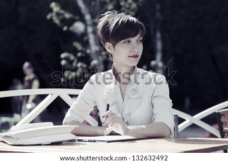 Young business woman at a sidewalk cafe