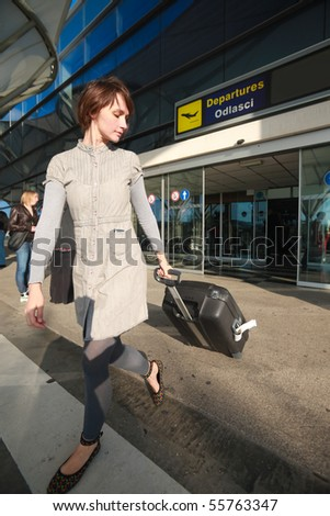 Young business woman at airport with luggage