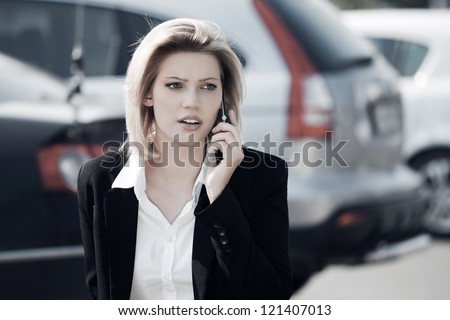 Young business woman calling on the phone against a city traffic