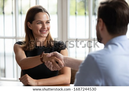 Young business woman client shake hand with company manager at office meeting. Insurer and customer closing deal, taking loan positive answer, real estate agent and buyer, job interview ending concept
