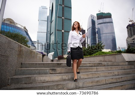 Young business woman descends the stairs to the street