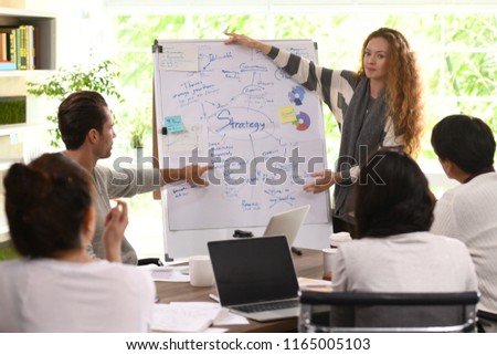Young business woman giving presentation on future plans to his colleagues at office #1165005103