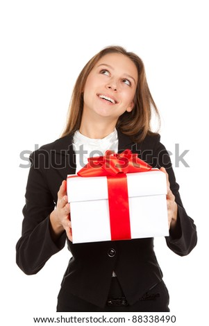 Young business woman happy smile hold white gift box with red bow in hands think and make a wish looking up to empty copy space. Isolated over white background