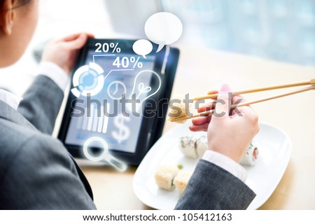 Young business woman having a business lunch at cafe with free wifi internet. She is looking at report of her company using her tablet computer
