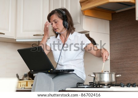 Young business woman having work conference call from home while cooking meal in kitchen