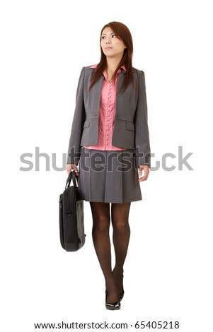 Young business woman holding briefcase and walking isolated over white.