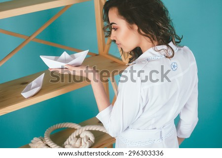 Young business woman holding paper boat with paper boat