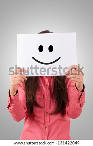 Young business woman holding paper with happy smiley on gray background.