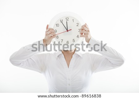 young business woman holds a big clock in front of her face