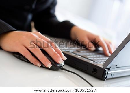 Young business woman in black blazer using a laptop