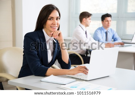 Young business woman in office smiling looking at camera