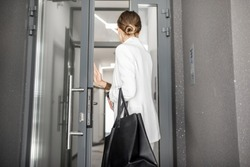 Young business woman in white suit entering to the hall of the modern residential building, back view
