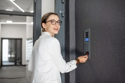 Young business woman in white suit touching the intercom with keychain opening the door of residential modern building