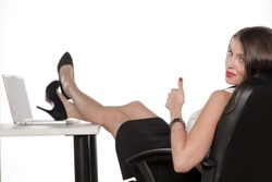 Young business woman is resting with feet up on a laptop on the table and showing thumbs up