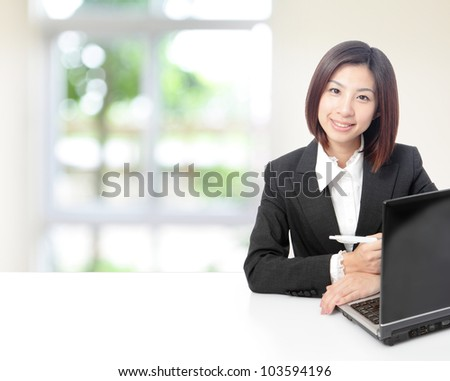 Young Business woman look to camera friendly, using computer and sit at company office with white table, window outside are green background, model is a asian beauty