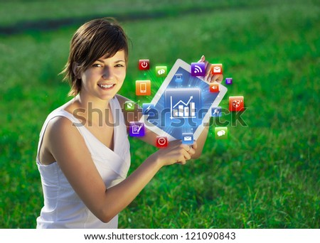 Young business woman looking at modern tablet with abstract lights and various icons - stock photo