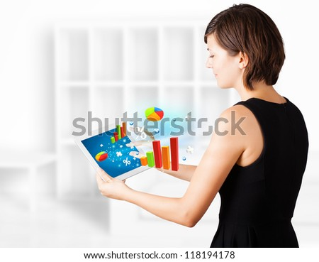 Young business woman looking at modern tablet with colourful diagrams