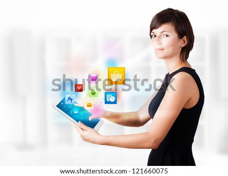 Young business woman looking at modern tablet with colourful icons