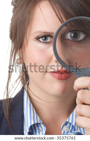 Young business woman looking at the camera through a magnifying glass, one eye magnified; close-up; isolated on a white background.