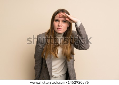Young business woman looking far away with hand to look something