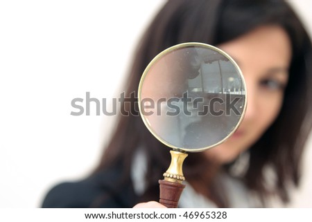 young business woman looks through a magnifier glass