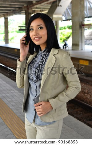 Young business woman making a phone call  in the train station