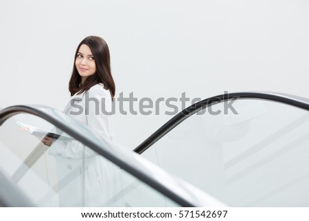 Young business woman on an escalator talking with mobile phone. Casual businesswoman in the modern office. Business concept