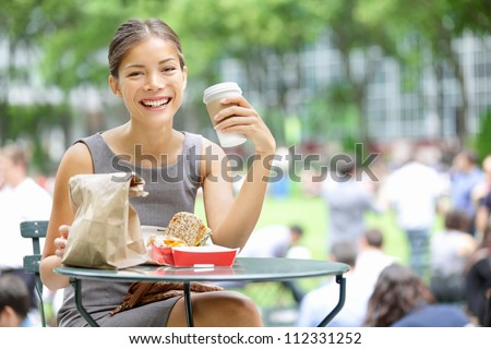Young business woman on lunch break in City Park drinking coffee and eating sandwich. Happy smiling multiracial young businesswoman in Bryant Park, New York City, USA.
