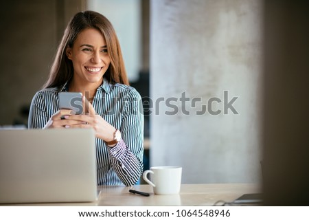 Young business woman on the phone at office. Business woman texting on the phone and working on laptop. Pretty young business woman sitting on workplace. Smiling business woman.