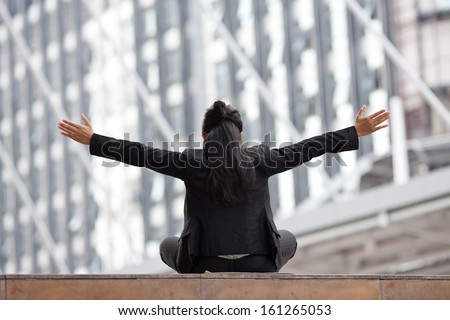 Young business woman outdoor sitting over building background