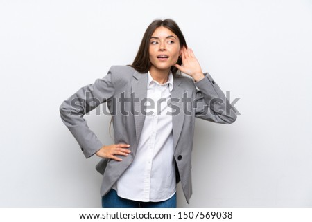Young business woman over isolated white background listening to something by putting hand on the ear Foto stock ©