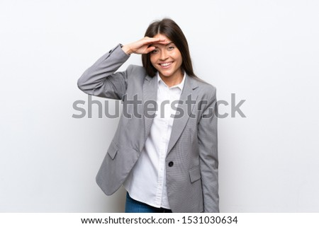 Young business woman over isolated white background looking far away with hand to look something