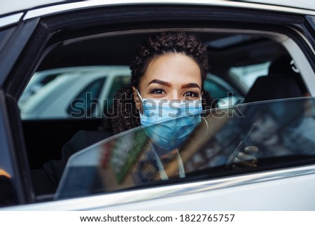 Young business woman passenger wearing a medical mask looks out of a taxi car window. Business trips during pandemic, new normal and coronavirus travel safety concept. Foto stock ©