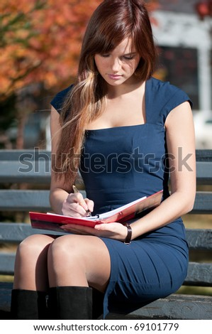Young business woman planing, writing and reviewing  diary at city park. Student