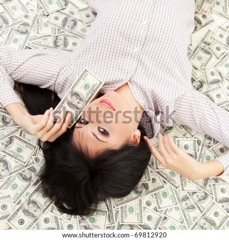 Young business woman resting upon money - stock photo